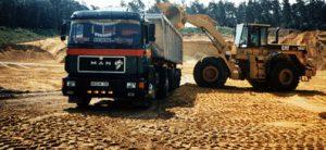 Sattelzugmaschinen Hollenberg an Baustelle mit Bagger